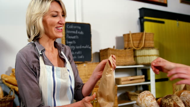 Female staff giving packed bread to woman at bakery section video