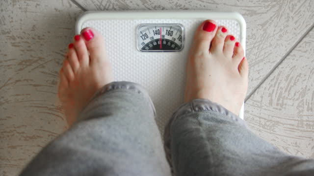 Female Standing on Weight Scale (HD) video
