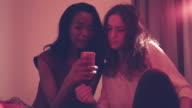 Female student friends in bedroom taking selfie video