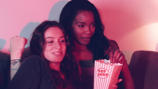 Female student friends on sofa eating popcorn video