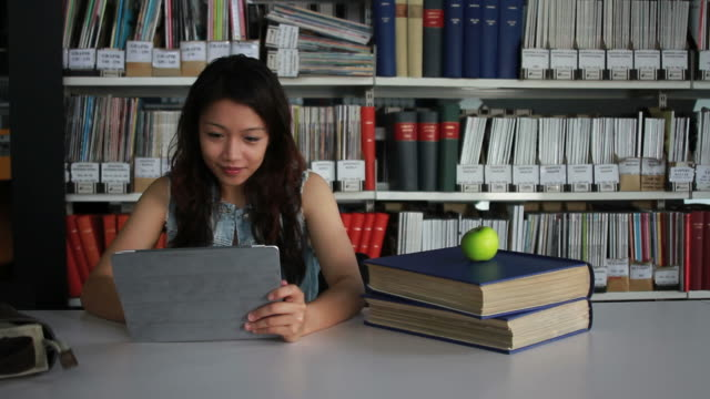 Female student in library working on digital tablet video