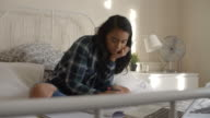 Female Student Sitting On Bed Studying With Notes And Laptop video