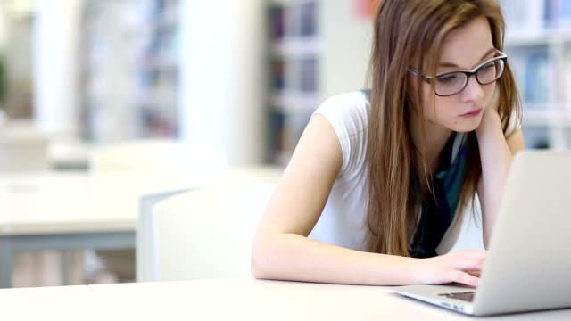 Female student working in a campus library video