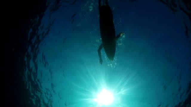 SLOW MOTION UNDERWATER: Female surfer paddling on a surf in open water ocean video