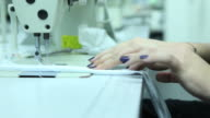 Female tailor working on sewing machine in factory video