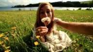 Female takes selfie portrait while blowing flower's seeds in meadow video