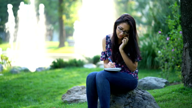 Female talking on the phone in the park and writing in the notebook video