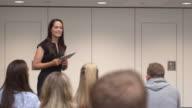 Female teacher addressing university students in class, shot on R3D video