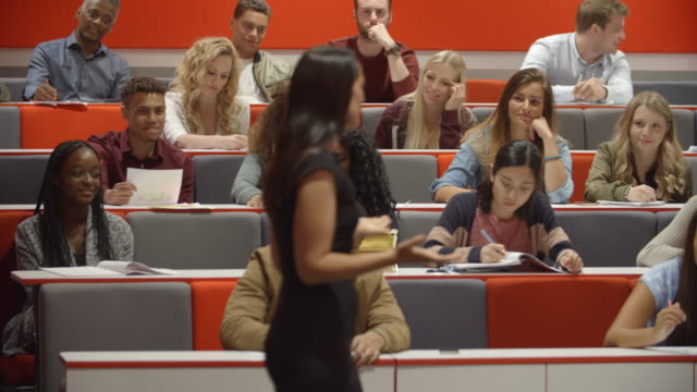Female teacher and students in university lecture theatre video