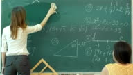 Female teacher at high school washes the chalkboard and lookng to the people in class video