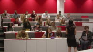 Female teacher presenting to students in a lecture theatre, shot on R3D video