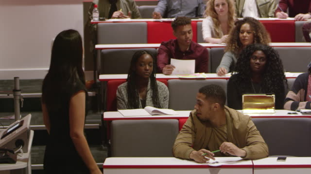 Female teacher talking with students in a lecture theatre, shot on R3D video