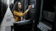 LD Female technician inserting hard discs in server room video