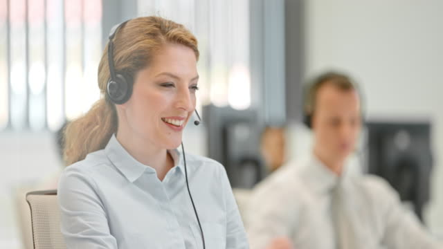 PAN Female telephone operator talking to a client video