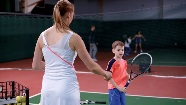 Female tennis instructor teaching boy how to hit the ball with a racquet video