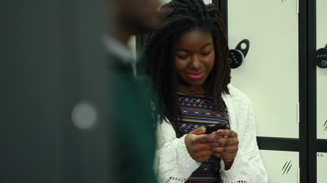 Female texting on phone in university video