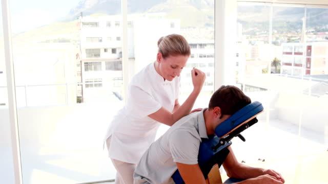 Female therapist massaging man sitting on massage chair video