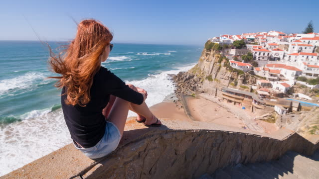 Female tourist overlooking a village on cliffs by the ocean video