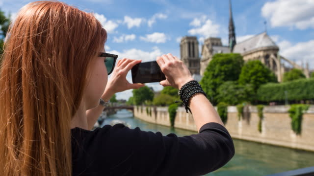 Female tourist taking pictures of Notre Dame de Paris video