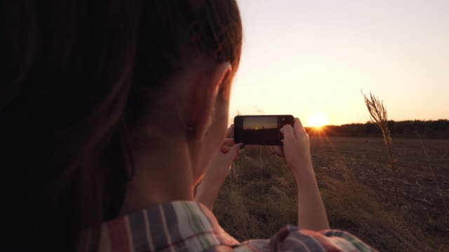 Female tourist taking pictures of the landscape at sunset. video