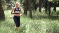 SLO MO DS Female trail marathon participant running through forest video