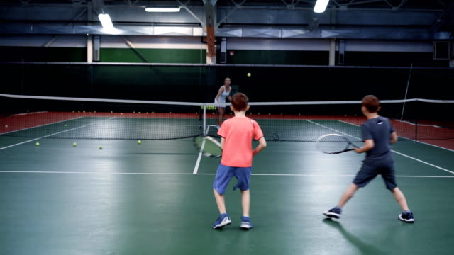 A female trainer in a sports suit teaches playing tennis in two middle-aged boys, guys are bouncing balls on a tennis court video