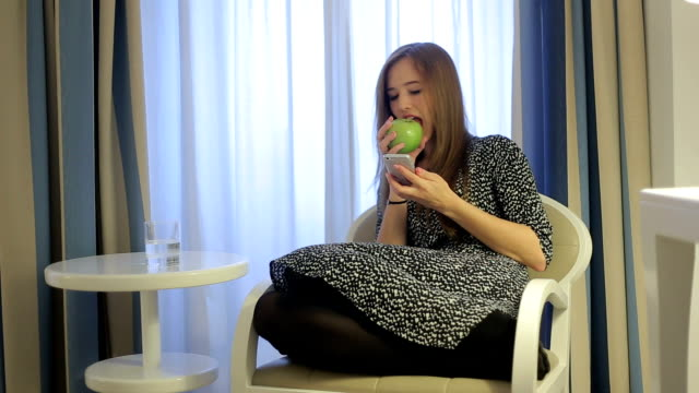 Female use smartphone seating in armchair and eat green apple video
