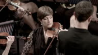 Female violin player watches conductor video