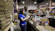 Female volunteer walking into focus while sorting donated food in charity warehouse video