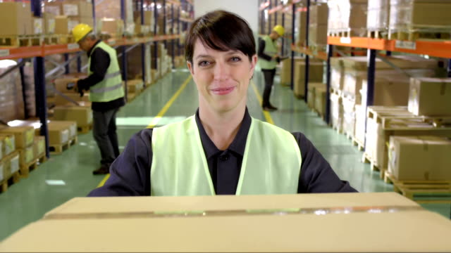 Female Warehouse Employee Handing Over A Box video