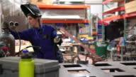 Female welder preparing in her workshop video