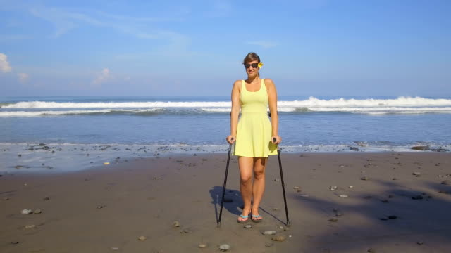 CLOSE UP Female with crutches and good health insurance on summer beach holidays video