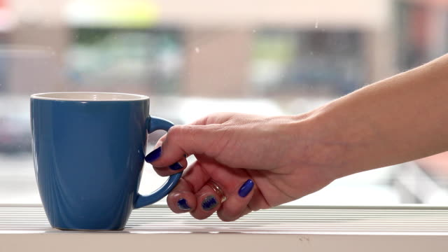 female woman hand take cup with hot tea coffee drink and snowflakes outdoor video