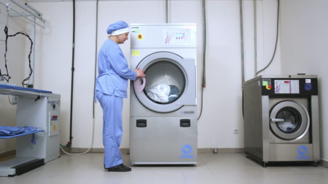 Female worker take away clothes from drying machine at laundry room video