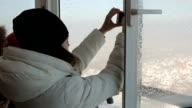 Female-photographer takes pictures with smartphone through open window of a high building in winter video
