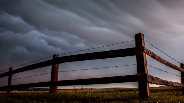 Fence in the field under stormy cloud sky. video