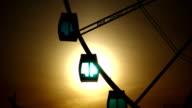 Ferris wheel cabins against bright evening sun shine through cyan glass video