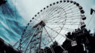 Ferris wheel in the amusement park against the backdrop of running thick clouds video