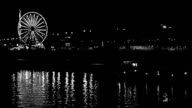 Ferris wheel reflection in river at night, black and white video