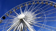 Ferris wheel rotating on blue sky background. video