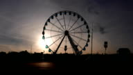 Ferris wheel slowly turn against evening sky at sunset video