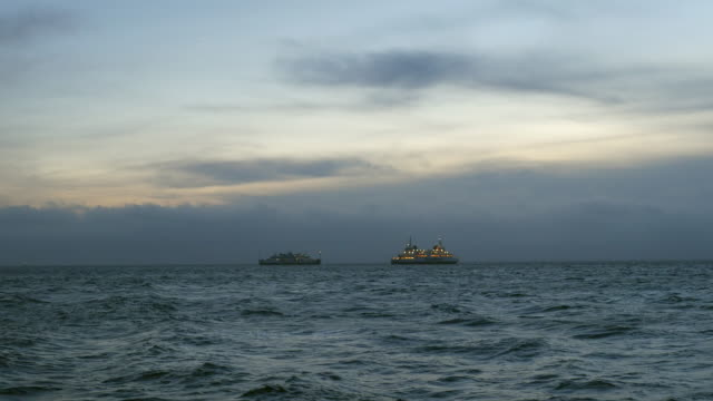 Ferry boats travel open sea at dusk video