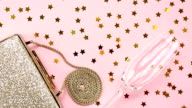 Festive evening golden clutch and champagne glass with star sprinkles shining on pink. Holiday and celebration background. Luxury accessories and party concept video