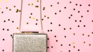 Festive evening golden clutch with star sprinkles on pink. Holiday and celebration background. Luxury accessories and party concept video