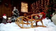 Festive sledges are among the Christmas trees. Parallax video