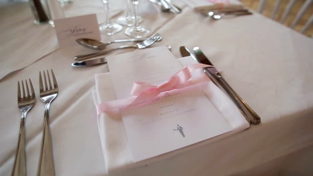 Festive table decoration arranged close up - menu and napkin tied with pink ribbon. Tableware set for special occasion of wedding banquet, anniversary reception or birthday lunch at luxury restaurant video