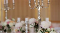 Festive table set for wedding or anniversary reception with candles in candelabrum and flowers close up shallow depth of field vertical pan. Tableware arrangement for several quests with place card video