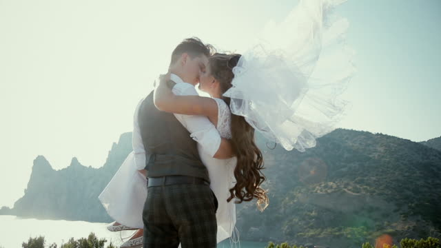 fiance holds his bride in his arms on the cliff video