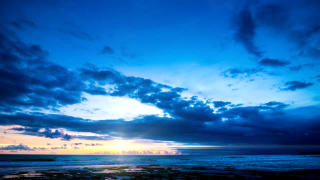 Fiery sunset in the blue sky over the ocean time lapse video