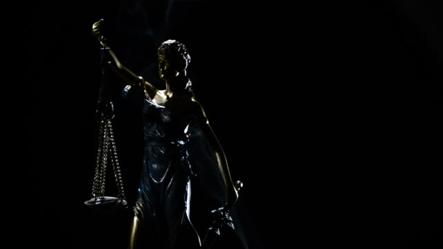 Figure of lady justice in rotation over black background with strands of smoke video